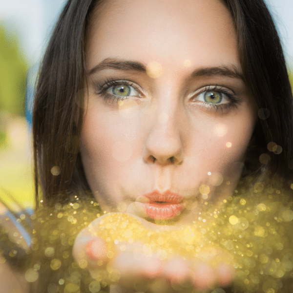 woman blowing glitter